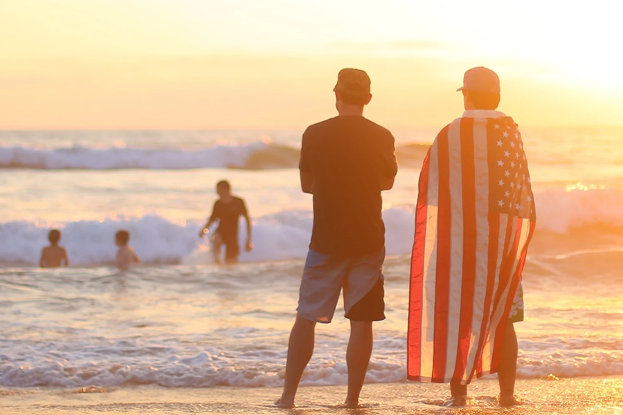 men standing on beach with American flag cape