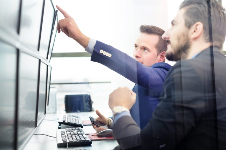 two traders pointing at screen