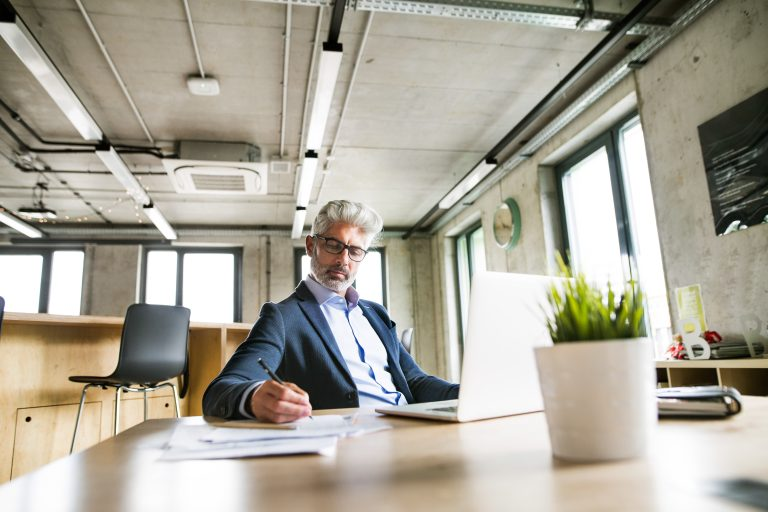 Mature businessman with laptop in the office